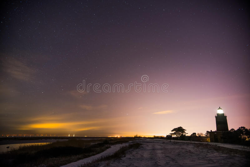 Lighthouse on coast at night royalty free stock photos