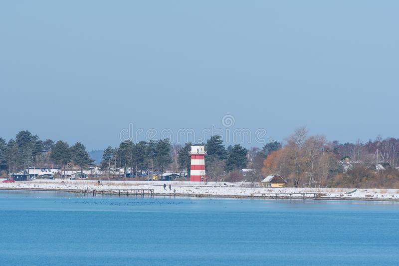 Lighthouse on the coast of town of Vordingborg in Denmark. On a snowy spring day stock photo
