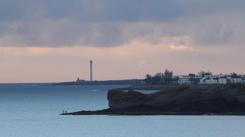 Lighthouse on coastline of Lanzarote, Canary Islands, Spain at sunset stock photos