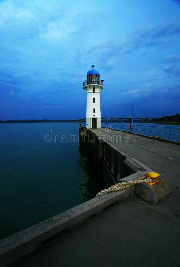 Lighthouse in the Dusk. A lighthouse in Singapore. Taken at dusk. Leading line formed by path along jetty in the foreground. White and blue colour of lighthouse stock photo