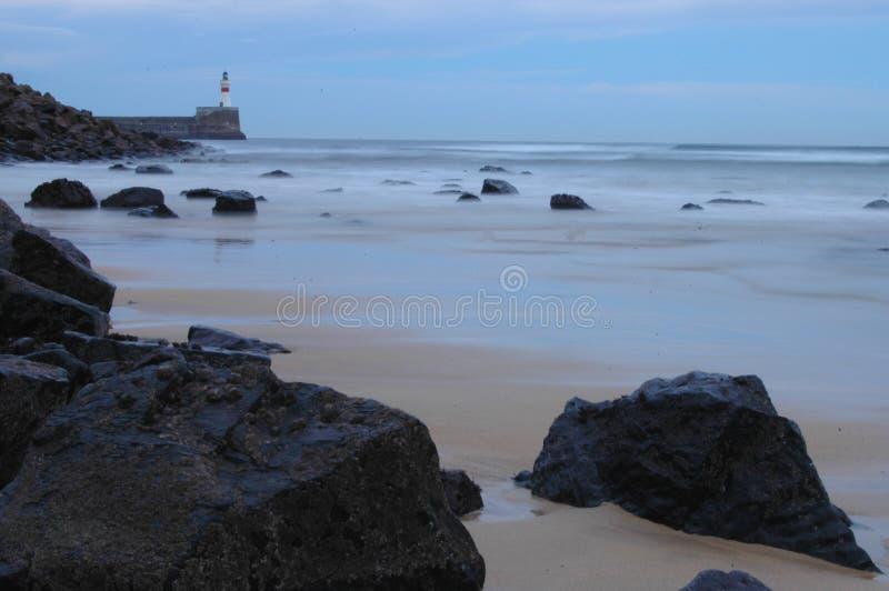 Lighthouse at dusk on a rocky coast royalty free stock photo