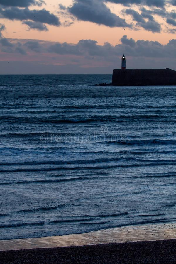 Lighthouse at the End of the Day. Newhaven Lighthouse and Seaford Beach at sunset with calm sea and clouds royalty free stock image