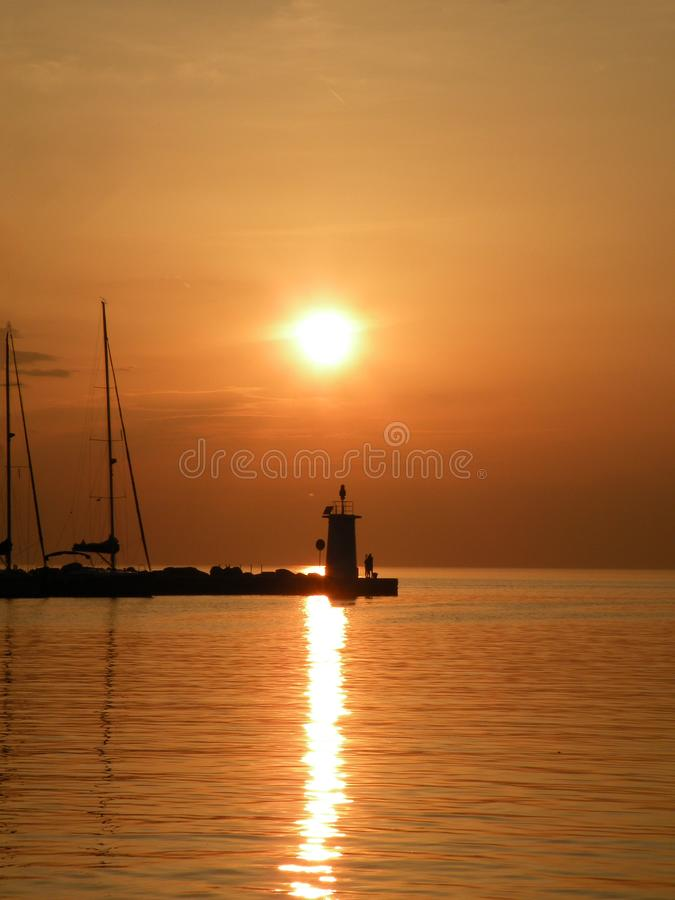 Lighthouse at the end of the pier of stones, sunset over the Adriatic Sea, Croatia, Europe.Orange, calm sea, silhouette, reflect royalty free stock photography