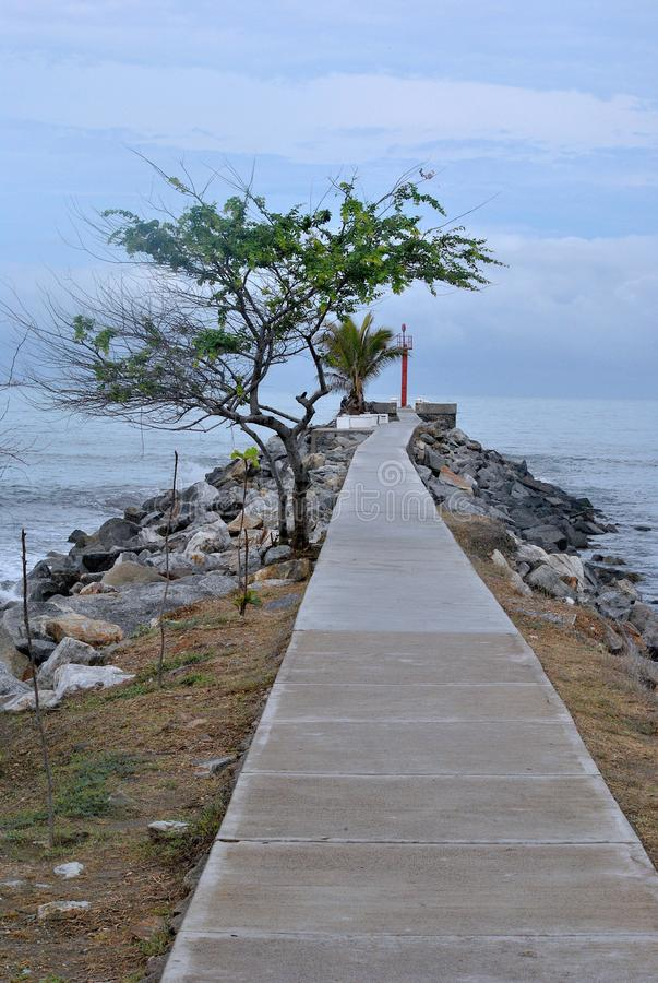 The lighthouse at the end of the road. On the sea, on Mexican beaches. Surrounded by trees and sea rocks stock images