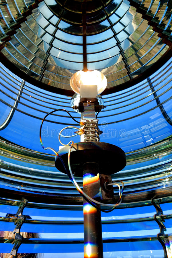 Lighthouse Fresnel with Guiding Beacon Light Bulb. Multifaceted glass Fresnel lens in a maritime navigation aid lighthouse with bright electric beacon light bulb royalty free stock photography