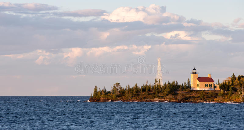 Lighthouse and Gathering Clouds in Evening Light. Lighthouse set on a peninsula and photographed in warm, evening light. Deep blue water, gathering clouds and stock photo