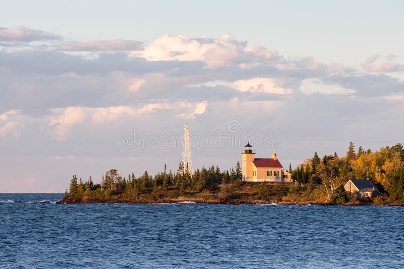 Lighthouse and Gathering Clouds in Evening Light. Lighthouse set on a peninsula and photographed in warm, evening light. Deep blue water, gathering clouds and royalty free stock photography