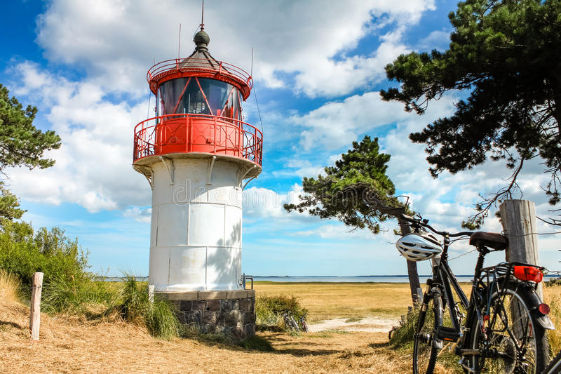 Lighthouse Gellen and bicycles. Sunny summer day. Hiddensee, Baltic Sea. Old lighthouse Gellen on sunny summer day. Bikes leaning on wooden fence posts. View to stock photo