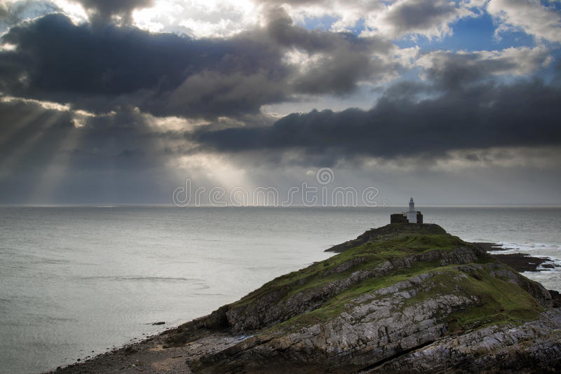 Lighthouse on headland with sun beams over ocean landscape with stock photography