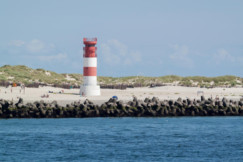 Lighthouse on Helgoland. At the beach with water, people and animals royalty free stock photo