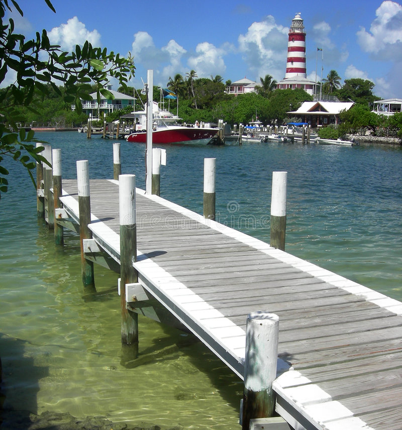 Lighthouse At Hope Town. The harbour and lighthouse at Hope Town on the island of Abaco in the Bahamas stock photo