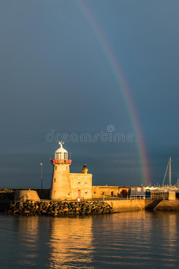 The lighthouse at Howth Harbour in County Dublin bathed in sunlight under a rainbow in front of a stormy sky stock photo