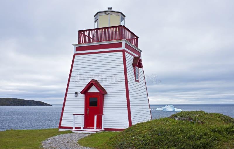 Lighthouse with iceberg, Newfoundland. Iceberg floats past Fox Point Lighthouse, St. Anthony, Newfoundland and Labrador, Canada stock images