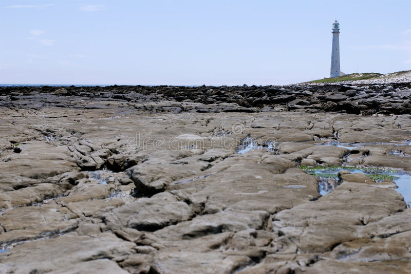 Lighthouse Kommetjie. Lighthouse of Kommetjie (Western Cape, South Africa) in background. In front stones stock photo