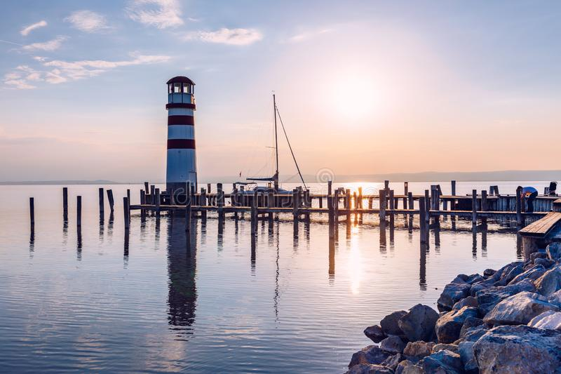 Lighthouse at Lake Neusiedl, Podersdorf am See, Burgenland, Austria. Lighthouse at sunset in Austria. Wooden pier with lighthouse royalty free stock photo