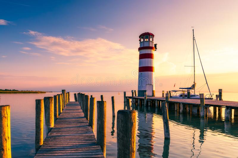 Lighthouse at Lake Neusiedl, Podersdorf am See, Burgenland, Austria. Lighthouse at sunset in Austria. Wooden pier with lighthouse royalty free stock images