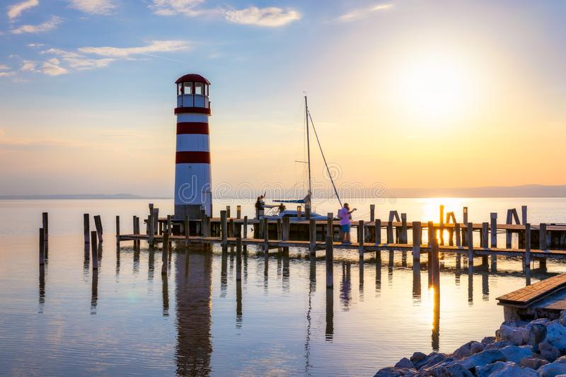 Lighthouse at Lake Neusiedl, Podersdorf am See, Burgenland, Austria. Lighthouse at sunset in Austria. Wooden pier with lighthouse stock image
