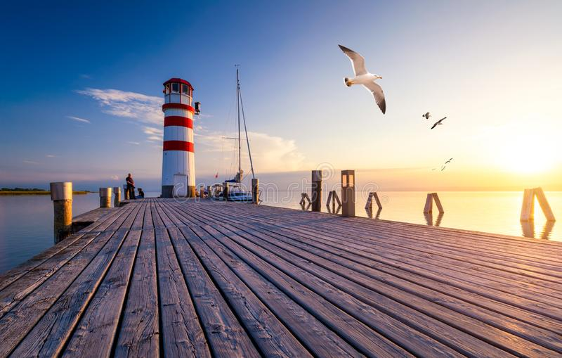 Lighthouse at Lake Neusiedl at sunset near Podersdorf with sea gulls flying around the lighthouse. Burgenland, Austria stock photo