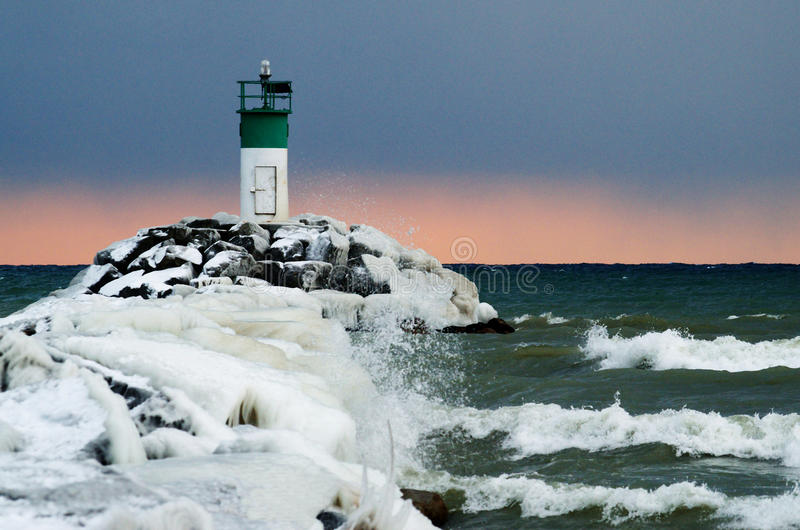 Lighthouse at lake ontario in winter with pink horizon, blue cloudy sky and waves crashing on the rocks stock photo