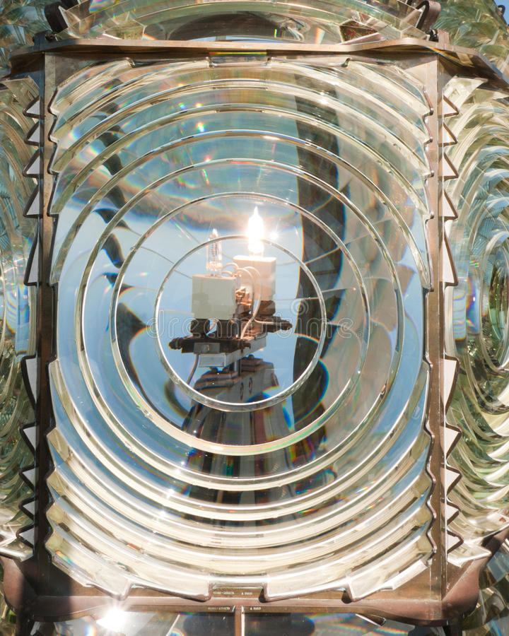 Lighthouse Lamp and Fresnel Lens. Antique Fresnel Lens sits atop Pacific Coast lighthouse. Inside you can see the Lamp is Lit, warning ships of the rocky coast stock image