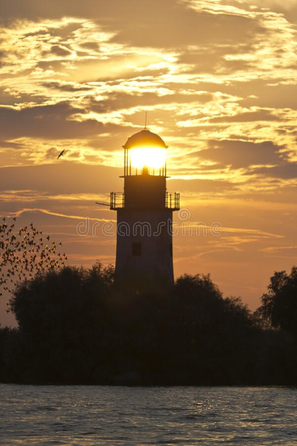 Lighthouse lit by setting sun stock photography