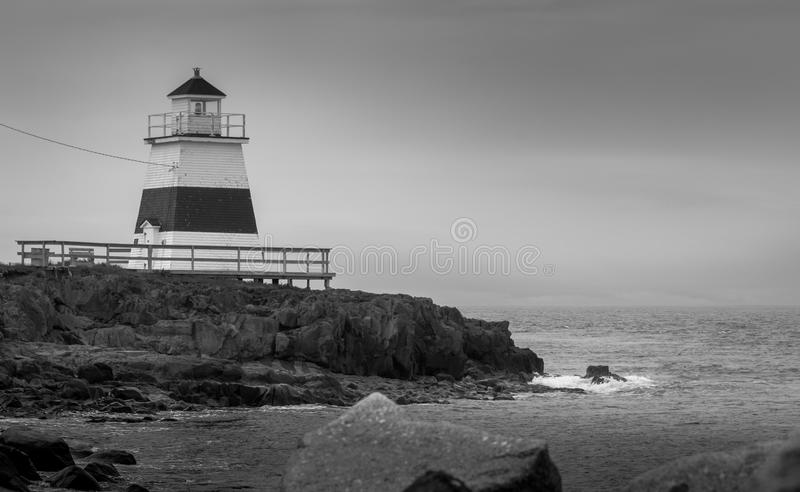 Lighthouse in Margaretsville, Nova Scotia. Overcast spring day in the Bay of Fundy. A lone lighthouse atop an outcropping of rock in the Bay of Fundy on an gray stock photo