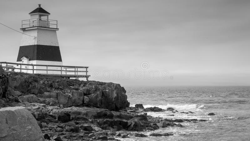 Lighthouse in Margaretsville, Nova Scotia. Overcast spring day in the Bay of Fundy. A lone lighthouse atop an outcropping of rock in the Bay of Fundy on an gray stock image