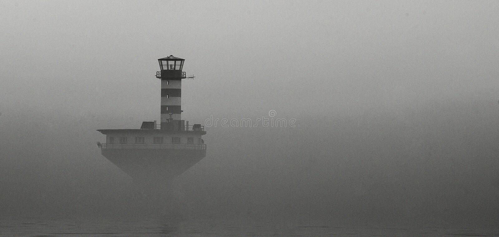 Lighthouse in the mist royalty free stock photography