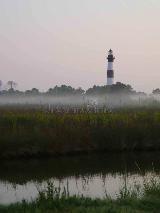 Lighthouse in the morning mist stock images