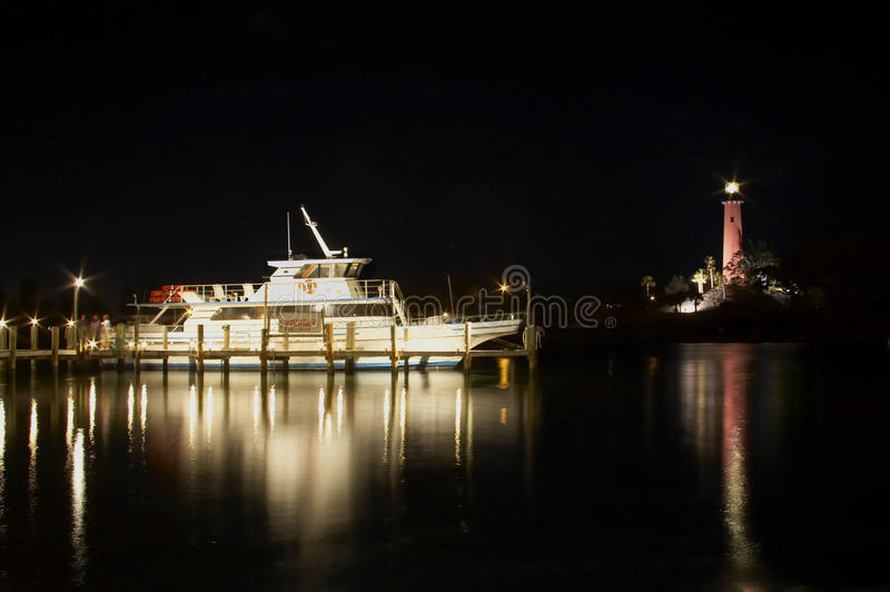 Lighthouse at night at night. Jupiter lighthouse at night with docked charter boat royalty free stock photos