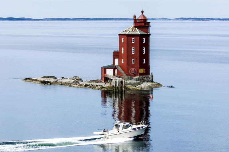 Lighthouse in Norway with motorboat in front, red wooden lighthouse royalty free stock photo