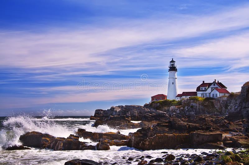 Lighthouse on the ocean, Portland. Maine United States. Stone cliffs on the raging waves. Sunny clear day. beautiful sky with gentle clouds royalty free stock images