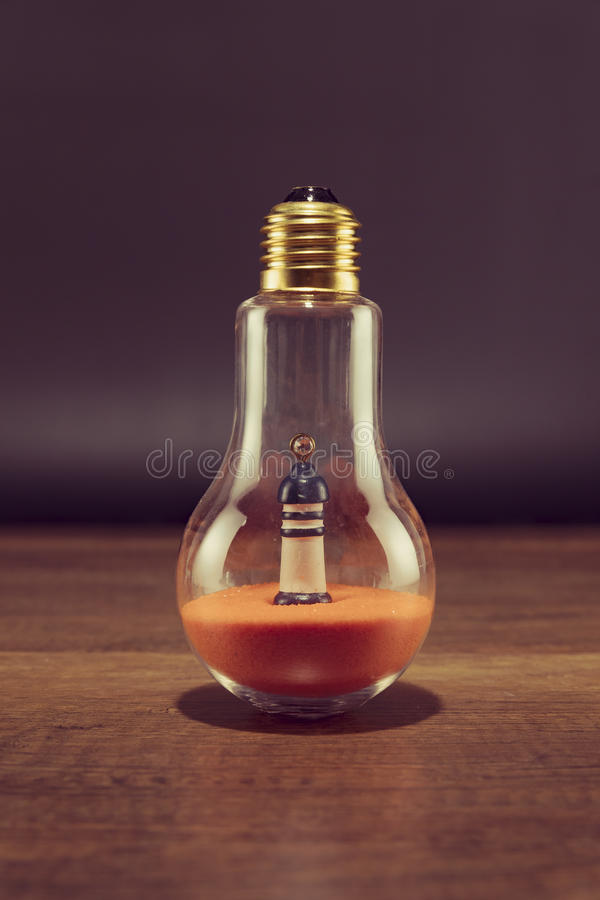 Lighthouse on orange sand in spiral bulb on wooden table. In Thailand stock image