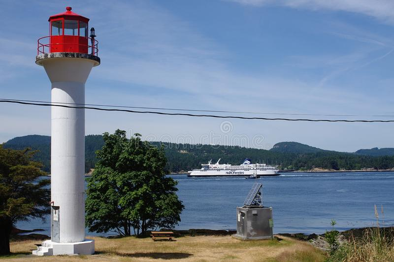 Lighthouse with passing ferry in the background. Georgia Point lighthouse on Mayne island  with BC Ferries, car and passenger ferry, in the background stock images
