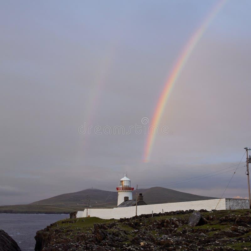Lighthouse with rainbow, Ireland stock image