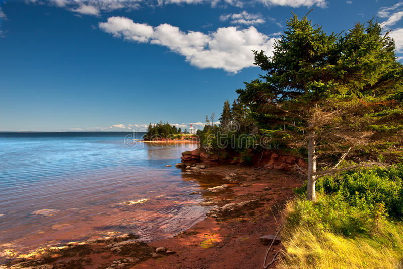 Lighthouse on red cliffs stock photography