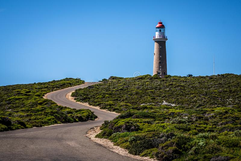 Lighthouse with red top and winding road at Cape du Couedic on Kangaroo island in Australia. Lighthouse with red top and winding road at Cape du Couedic on royalty free stock photography