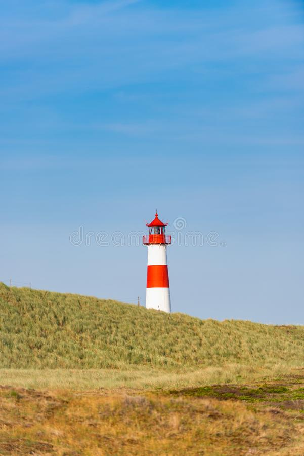 Lighthouse red white on dune. Vertical. Focus on background with lighthouse royalty free stock photo
