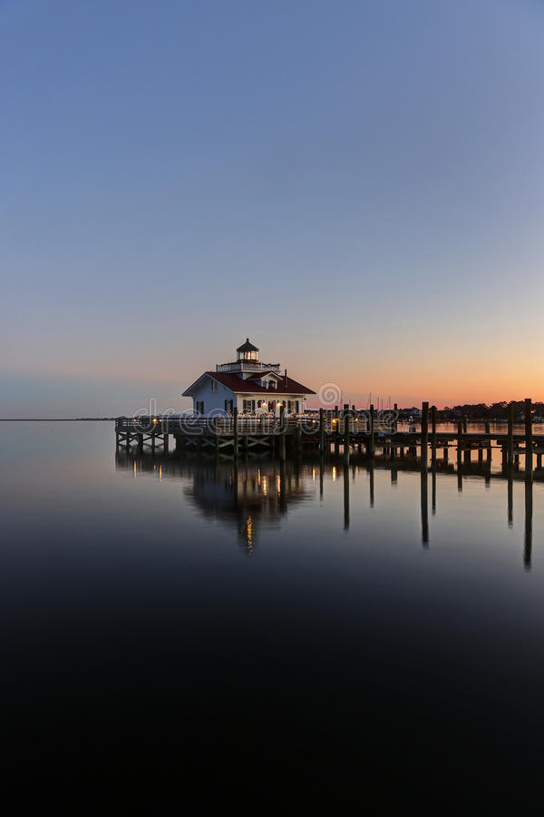 Lighthouse reflected in water at dusk. Roanoke Marshes Lighthouse Manteo NC Outer Banks North Carolina dock in Albemarle Sound royalty free stock photos
