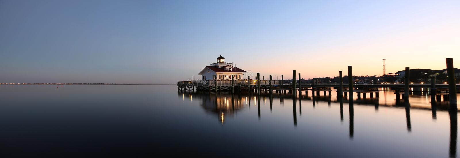 Lighthouse reflected in water at dusk. Roanoke Marshes Lighthouse Manteo NC Outer Banks North Carolina dock in Albemarle Sound royalty free stock images