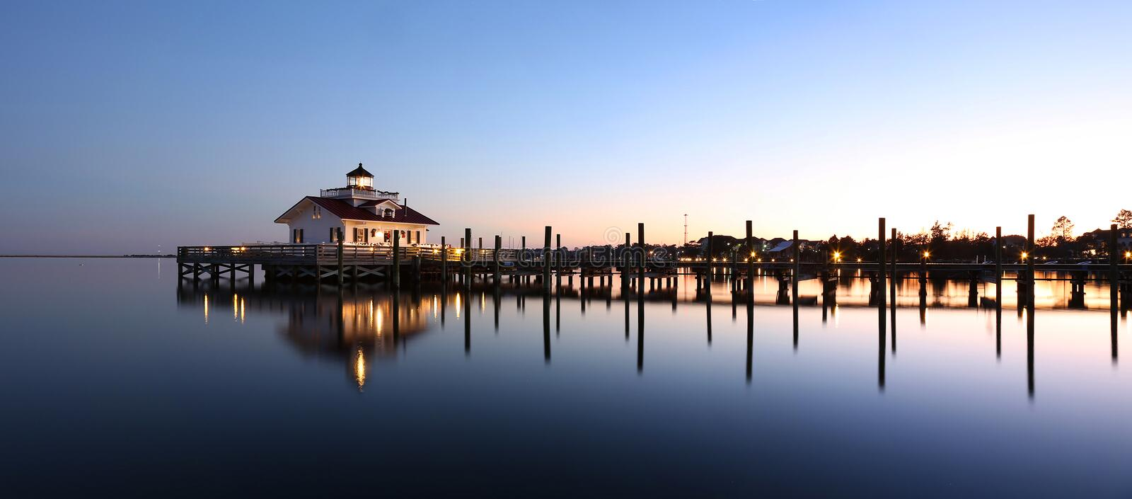 Lighthouse reflected in water at dusk. Roanoke Marshes Lighthouse Manteo NC Outer Banks North Carolina dock in Albemarle Sound stock photo