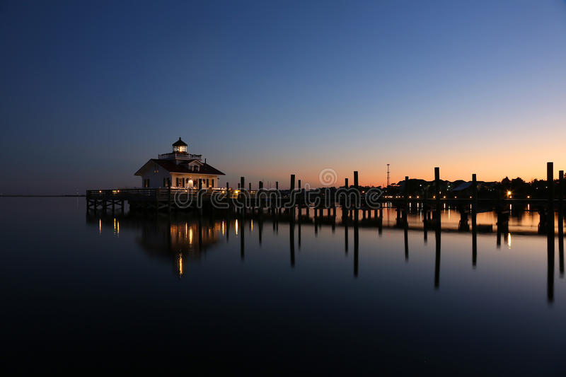 Lighthouse reflected in water at dusk. Roanoke Marshes Lighthouse Manteo NC Outer Banks North Carolina dock in Albemarle Sound stock photos