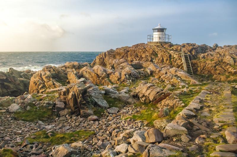 Lighthouse on a rocky shore during a sunset royalty free stock photos