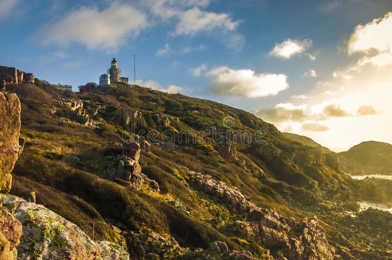 Lighthouse on a rocky shore during a sunset stock photos