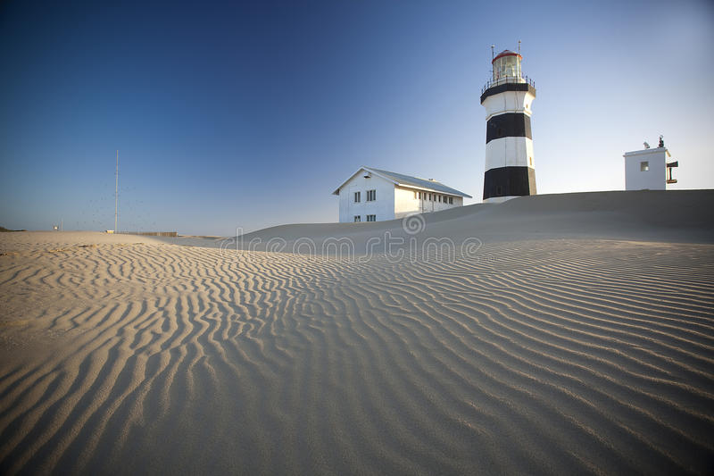 A lighthouse on sand dunes royalty free stock photos