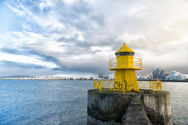 Lighthouse on sea pier in reykjavik iceland. Lighthouse yellow bright tower at sea shore. Sea port navigation concept. Sea transportation and navigation stock photography