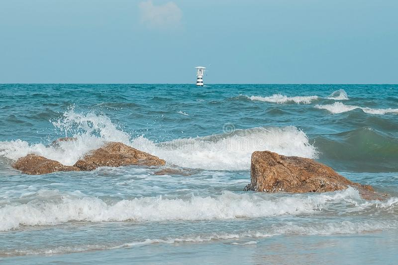 Lighthouse on the sea with Thailand flag and Sea wave and Splashes  hits the stone on the beach. Pastel tone stock photos