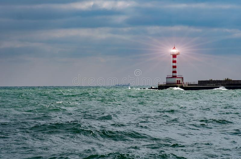 Lighthouse searchlight beam through marine air. Lighthouse In Stormy Landscape - Leader And Vision Concept royalty free stock photo
