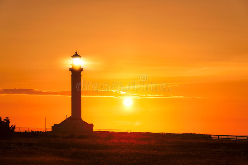 Lighthouse searchlight beam at sunset stock images