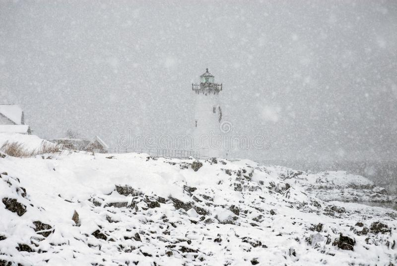 Lighthouse in Snowstorm by Rocky Coast in New England. Portsmouth Harbor lighthouse shines a bright green light over the rocky shore during a snowstorm in New stock photos